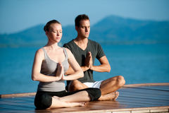 Yoga Couple By Ocean. An attractive young woman and man doing yoga on a jetty with the blue ocean and another island behind them