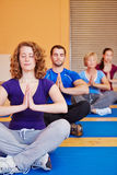 Yoga course in fitness center. Yoga course with men and women meditating in a fitness center Royalty Free Stock Photo