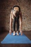 Yoga d'allungamento e di pratica dell'atleta della donna sulla stuoia Immagine Stock