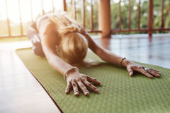 Yoga d'esecuzione femminile di balasana di forma fisica alla palestra fotografia stock