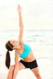 Yoga, das Frau auf Strand ausdehnt Stockbilder