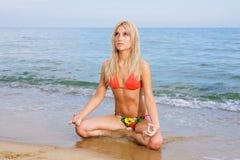 Yoga, das am Strand übt Stockbild