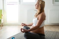 Yoga de détente et de pratique de femme enceinte à la maison image stock