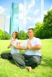 Yoga de deux Caucasiens en stationnement du centre Photo libre de droits