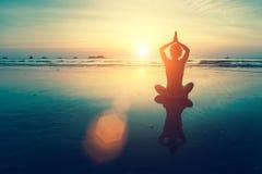 Yoga de femme de silhouette sur la plage d'océan Photographie stock libre de droits