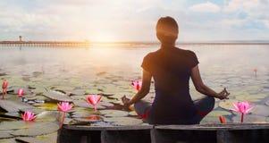 Yoga de femme pratiquant et méditant par le backg rouge de lac de lotus photos libres de droits