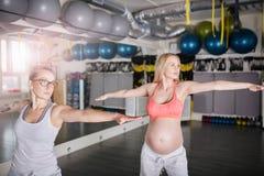 Yoga de formation de femme enceinte étirant des exercices avec personnel images stock
