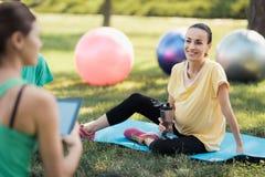 Yoga de grossesse L'entraîneur s'assied devant un groupe de femmes enceintes et regarde quelque chose sur son comprimé Images libres de droits