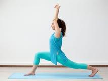 yoga De jonge donkerbruine vrouw in strijder stelt Stock Foto's