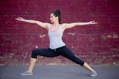 Yoga de la calle: Actitud de Virabhadrasana 2 Imágenes de archivo libres de regalías
