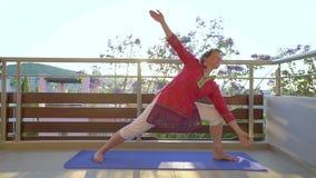 Yoga de la mañana Mujer que hace yoga en su terraza del apartamento almacen de metraje de vídeo