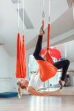 Yoga de la mosca La mujer joven practica yoga antigravedad aérea con una hamaca fotos de archivo