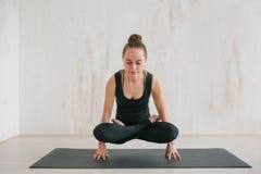 Yoga de la mujer hermosa joven y gimnástico practicantes Concepto de la salud Hace un ejercicio del poder que se coloca en sus fi Imágenes de archivo libres de regalías