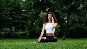Yoga de la mujer joven en el parque que habla en un teléfono almacen de video