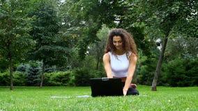 Yoga de la mujer joven en el parque que trabaja en un ordenador portátil almacen de video