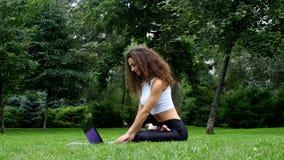 Yoga de la mujer joven en el parque que trabaja en un ordenador portátil almacen de metraje de vídeo