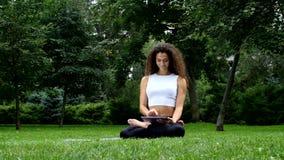 Yoga de la mujer joven en el parque que trabaja en una tableta almacen de video