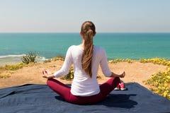 Yoga de la mujer joven en la playa del mar Fotografía de archivo