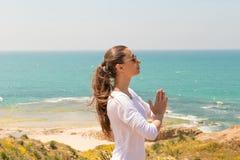 Yoga de la mujer joven en la playa del mar Fotos de archivo