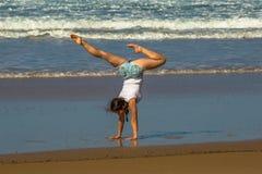 Yoga de la práctica de la mujer del gimnasta en la playa Foto de archivo