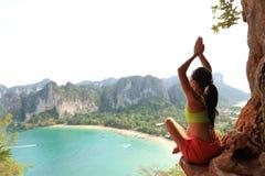 yoga de la práctica de la mujer en el acantilado de la roca de la playa Imagenes de archivo