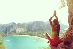 yoga de la práctica de la mujer en el acantilado de la roca de la playa Fotografía de archivo