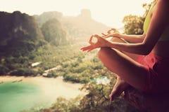 Yoga de la práctica de la mujer en el acantilado del pico de montaña Foto de archivo libre de regalías