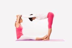 Yoga de la práctica de la mujer mayor y más joven Foto de archivo libre de regalías