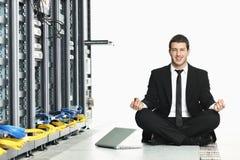 Yoga de la práctica del hombre de negocios en el sitio de servidor de red Imagen de archivo libre de regalías