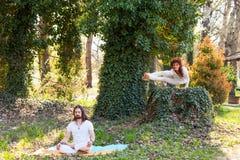 Yoga de la práctica del hombre joven y de la mujer al aire libre en el día de verano de madera imagenes de archivo