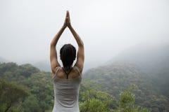 yoga de la práctica en el top de niebla de la montaña de la primavera Imagenes de archivo