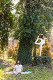 Yoga de la pr?ctica del hombre joven y de la mujer al aire libre en el d?a de verano de madera imagen de archivo
