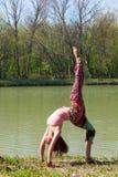 Yoga de la pr?ctica de la mujer joven al aire libre por el tiro lleno del cuerpo del concepto sano de la forma de vida del lago fotografía de archivo libre de regalías