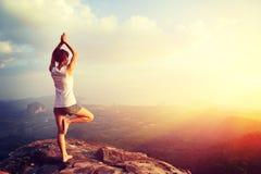 Yoga de la práctica de la mujer en la playa de la salida del sol Imagenes de archivo