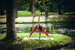Yoga de la práctica de la mujer joven al aire libre Fotos de archivo