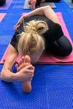 Yoga de las prácticas de la mujer joven doblada al pie Fotografía de archivo