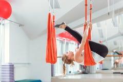 Yoga de mouche La jeune femme pratique le yoga anti-gravité aérien avec un hamac photographie stock libre de droits