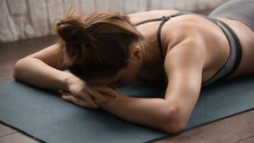 Yoga de pratique de belle femme, détendant après avoir formé, visage menteur vers le bas image libre de droits
