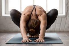 Yoga de pratique de belle femme, se reposant dans la pose de guirlande, exercice de Malasana photographie stock