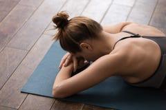 Yoga de pratique de belle femme, visage menteur vers le bas, détendant après la formation photos libres de droits