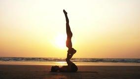 Yoga de pratique d'acro de couples sportifs convenables avec l'associé ensemble sur la plage sablonneuse banque de vidéos