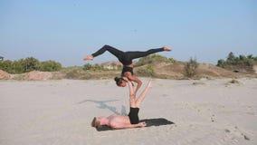 Yoga de pratique d'acro de couples sportifs convenables avec l'associé ensemble sur la plage sablonneuse clips vidéos