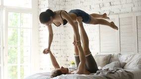 Yoga de pratique d'acro de jeunes couples sportifs convenables ensemble sur le lit banque de vidéos