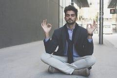 Yoga de pratique d'homme d'affaires caucasien sur le trottoir images libres de droits
