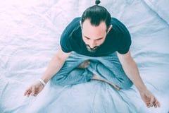 Yoga de pratique d'homme décontracté paisible à la maison image libre de droits