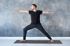 Yoga de pratique d'homme dans le studio faisant la pose du guerrier 2 photo libre de droits