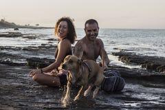 Yoga de pratique de couples heureux sur le lever de soleil Photo stock