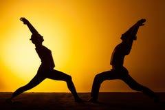 Yoga de pratique de deux personnes dans la lumière de coucher du soleil Images stock