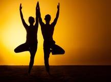 Yoga de pratique de deux personnes dans la lumière de coucher du soleil Photographie stock