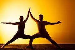 Yoga de pratique de deux personnes dans la lumière de coucher du soleil Photo libre de droits